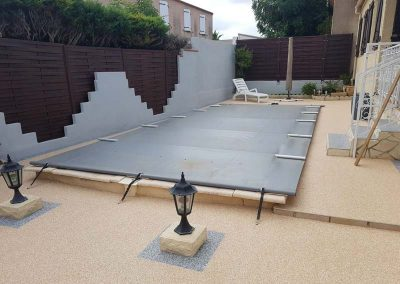 Rénovation d'une terrasse en granulat de marbre avec habillage de la piscine sur mesure en bois exotique :